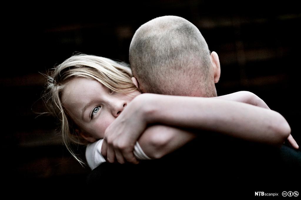 Far og datter holder rundt hverandre. Faren med snauklipt hode, og med ryggen til. Dattera med ansiktet mot betrakteren. Hun har lyst hår og blå øyne og ser alvorlig ut. Foto.