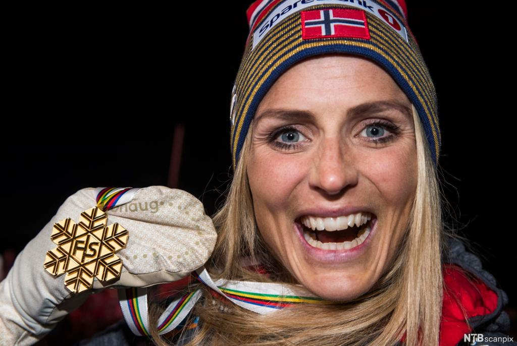 En smilende jente med gullmedalje. Foto.