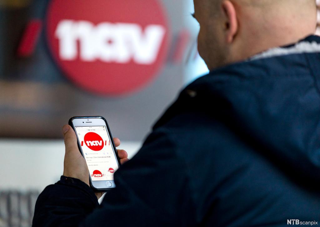 En mann holder en mobiltelefon med NAV-app utenfor et NAV-kontor. Foto.