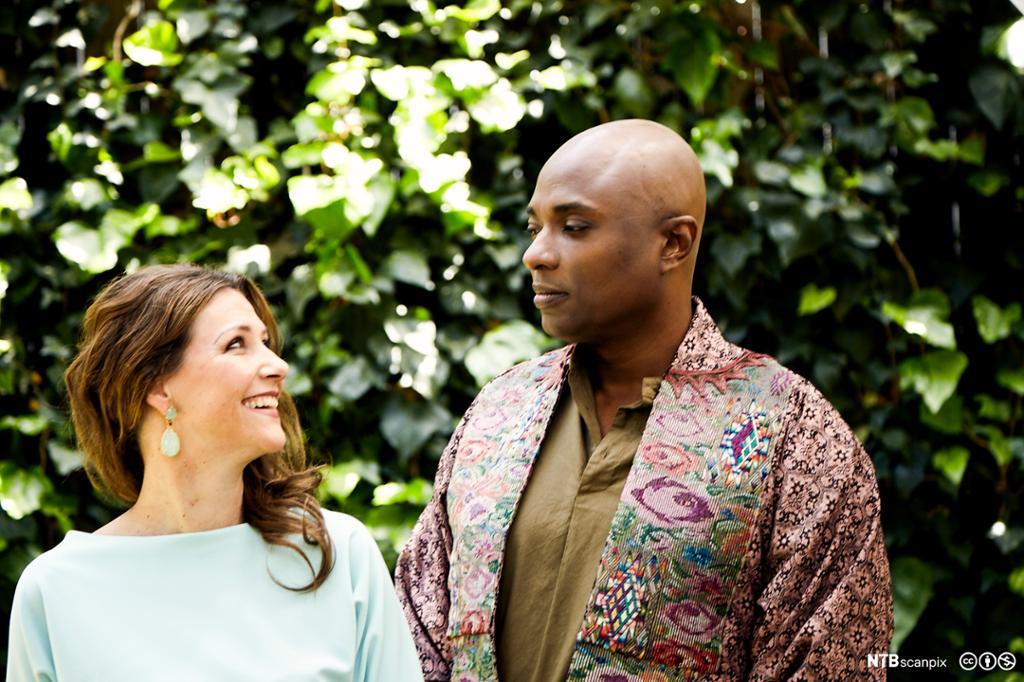En ung hvit kvinne ser kjærlig på en mørkhudet mann. Foto.