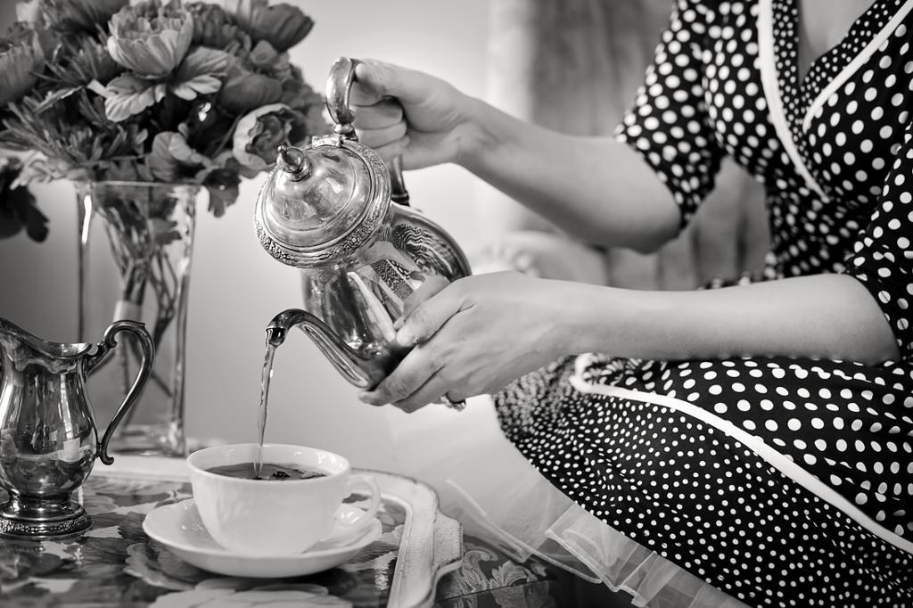 Dame i grå og hvit penkjole heller i te i kopp. Foto.