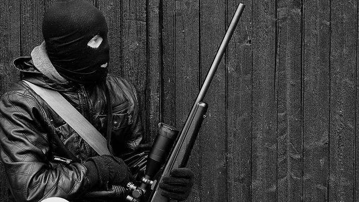 En maskert mann med skytevåpen. Foto.