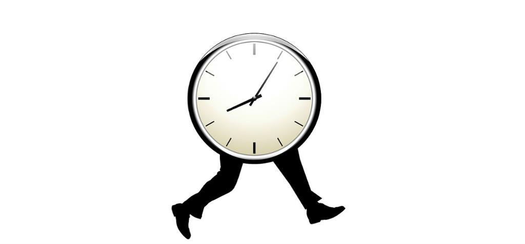 Stor klokke med ben som løper i en retning. foto.