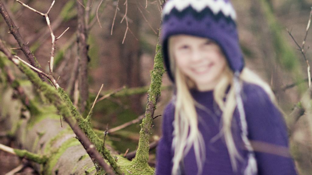 Jente fotografert i skogen. Fokusfeil har oppstått i bildet. Modellen er uskarp. Foto.