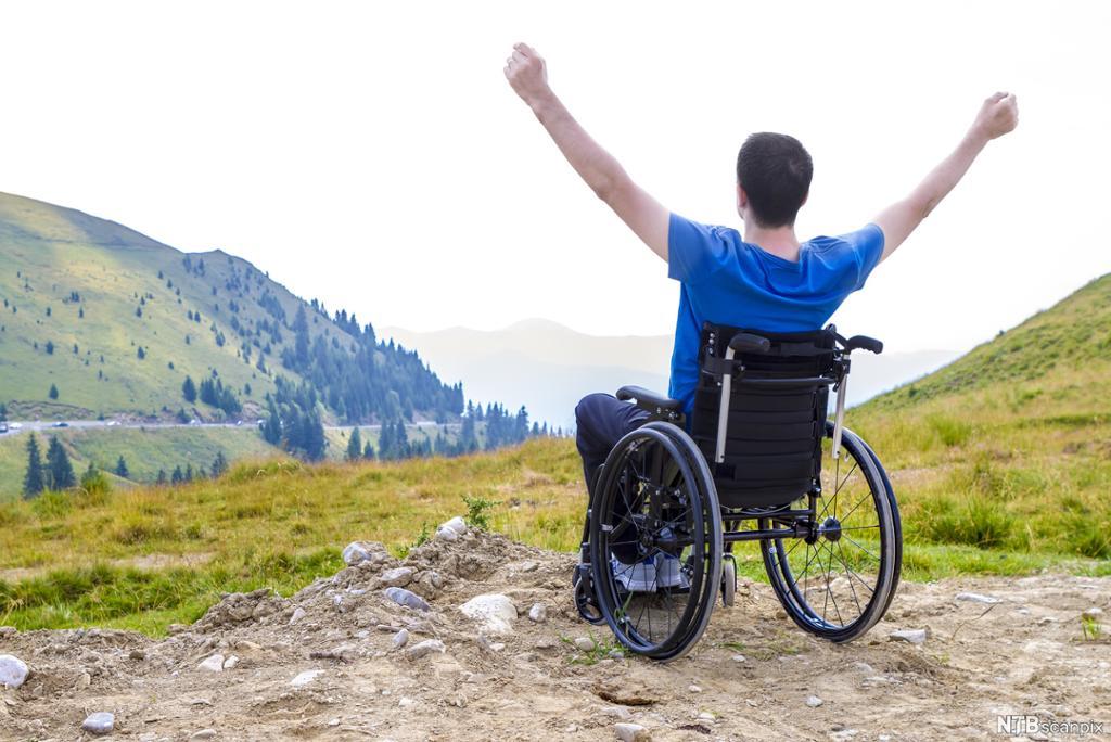 Mann i rullestol i fjellandskap. Foto.