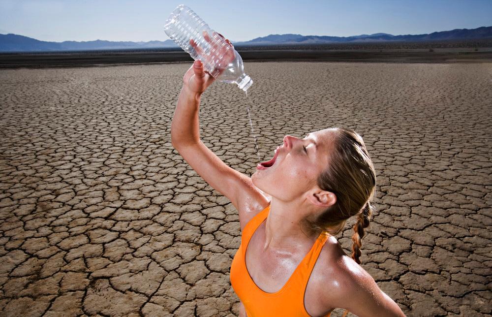 Dame har mangel på vann i ørkenen. Foto.