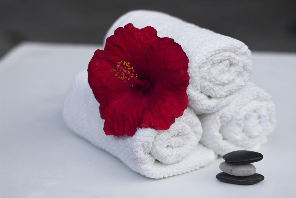 Tre sammenrullede hvite håndklær med en stor rød blomst oppå. Ved siden av er det en stabel med tre flate, glatte steiner. Foto.