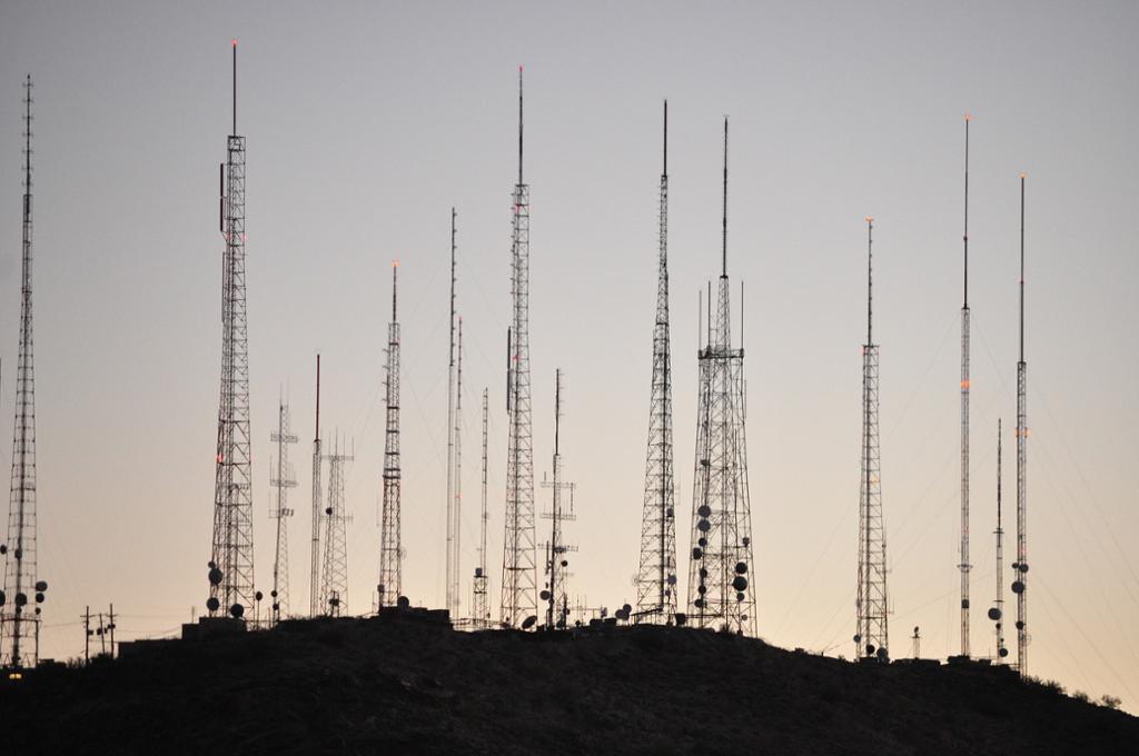 Flere høye radiomaster på en bakketopp i horisonten. Foto.