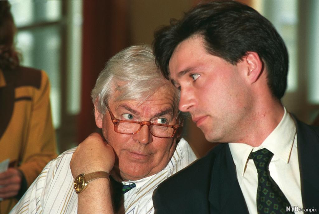 En yngre og en eldre mann snakker sammen. Foto.