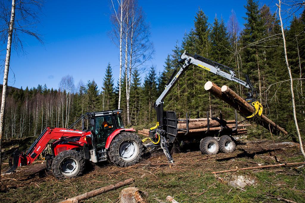Traktor med tømmerhenger og kran. Foto.