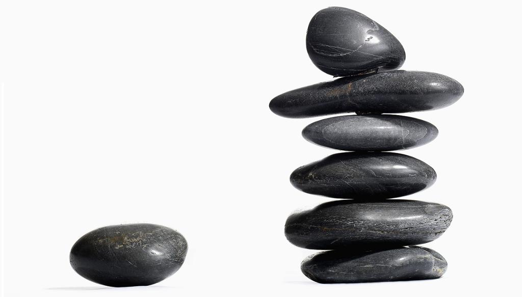 En stein som ligger alene og en stabel med seks steiner. Foto.