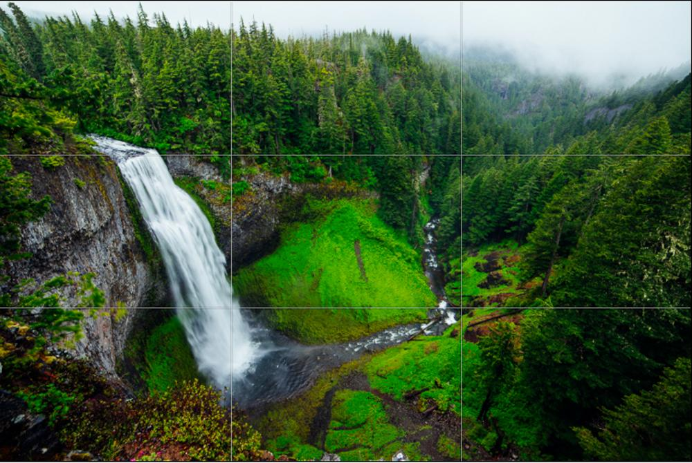 Foss som stuper utfor skrent i grønt skoglandskap. Fotografi.