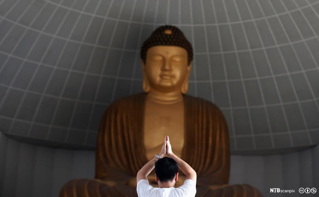 Mann står foran buddhastatue. Han holder hendene over hodet med håndflatene mot hverandre. Foto.
