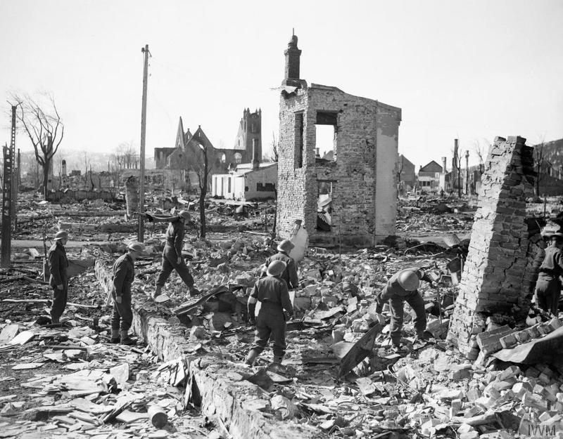 Britiske soldater går gjennom et utbombet Namsos etter tyskernes bombeangrep, april 1940. Foto.