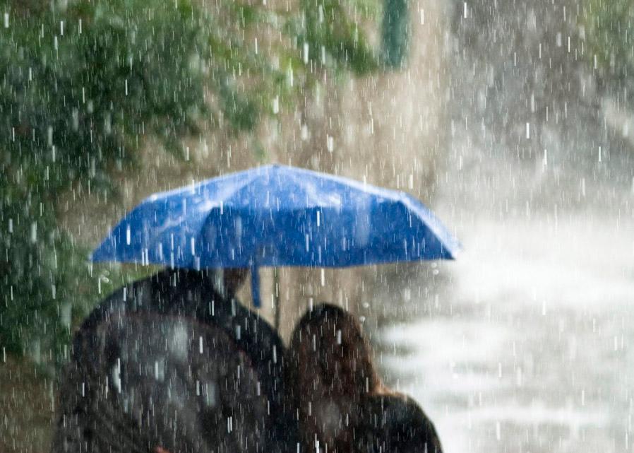 To mennesker som søker ly under samme paraply under en kraftig regnbyge.