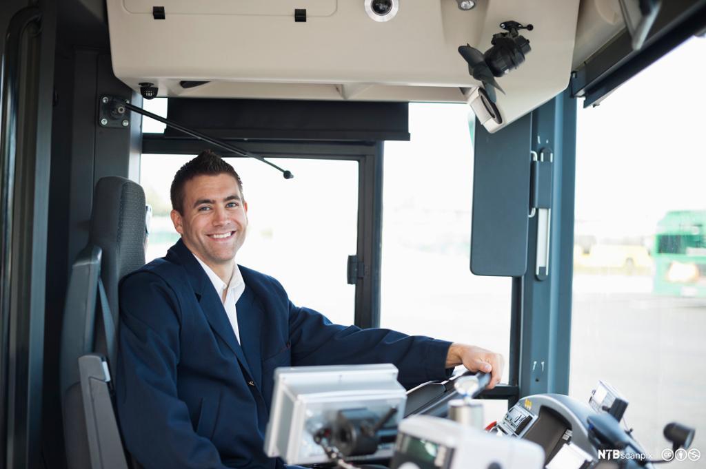Et fotografi av en blid bussjåfør