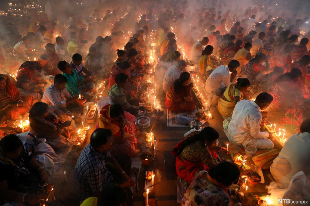 Stor folkemengde sitter sammen på gulvet med levende lys foran seg. Foto.