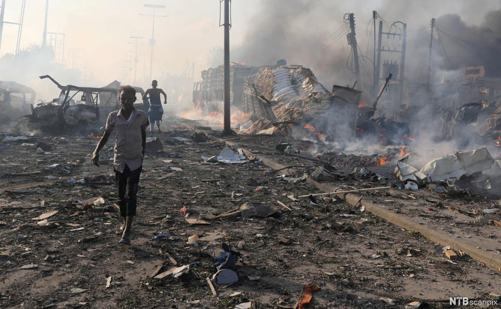 Explosion in Mogadishu, Somalia. Burning cars and debris in the street, with a few civilians leaving the area. Photo.