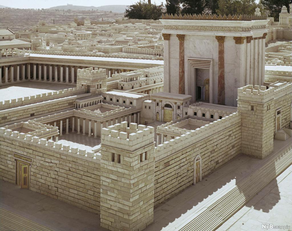 Modell av monumental murbygning. By i bakgrunnen. Foto.
