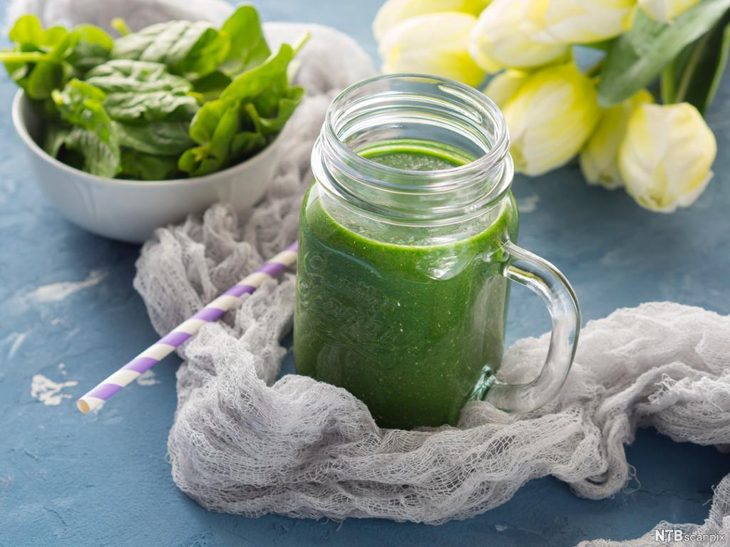Glass med grønn drikke med blomster og grønne blader i bakgrunnen. Foto.
