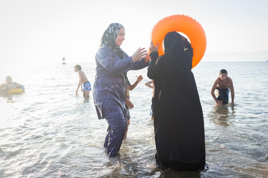 To kvinner kledd i heldekkende badedrakter og hodeplagg leker i vannkanten. Foto.