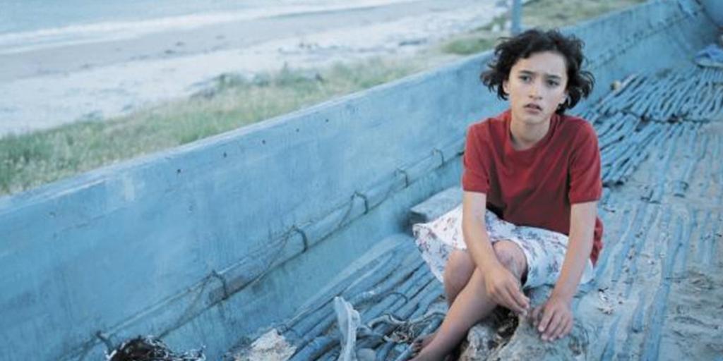 En jente i rød t-skjorte sitter på en strand. Foto.