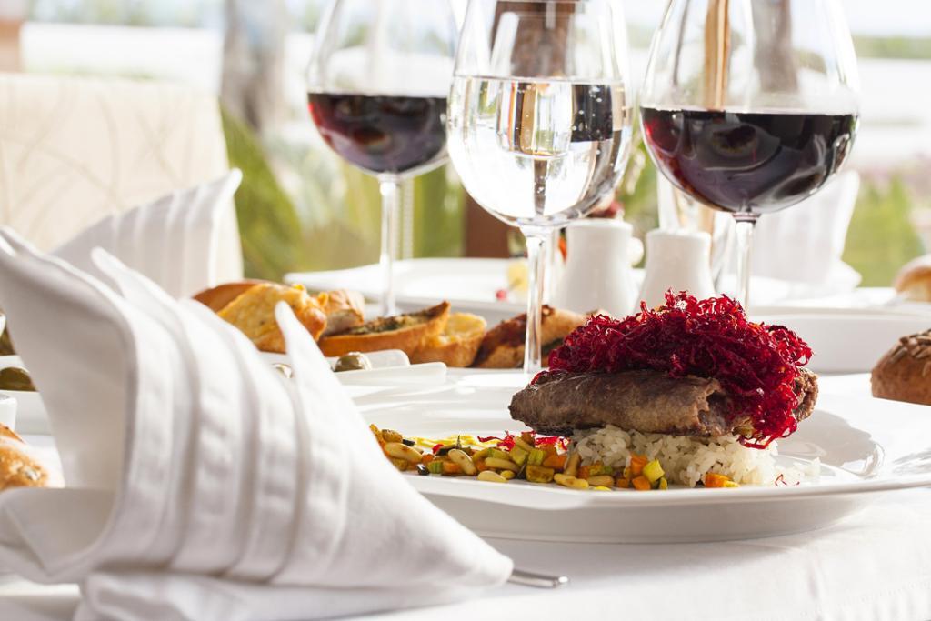 Tallerken med middagsrett, stettglass med vin og serviett på restaurantbord.foto