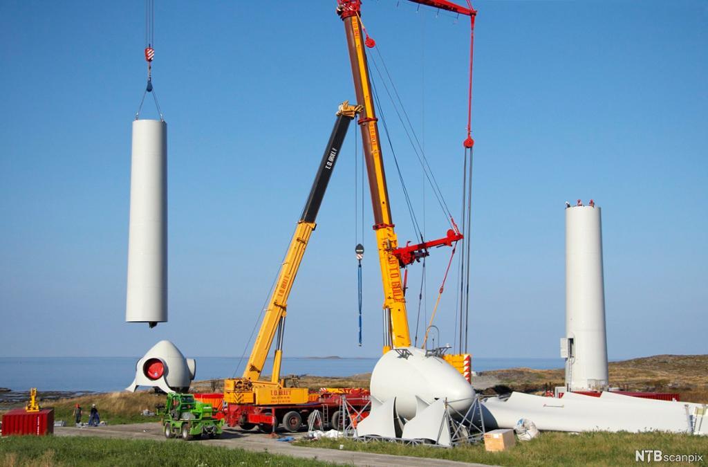 Mobilkran heiser på plass deler av vindturbin i naturområde. Foto.