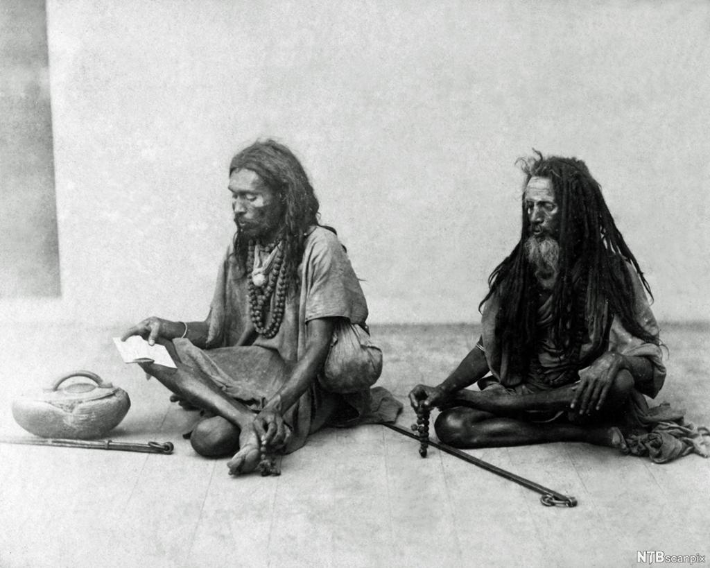 To menn sit på golvet. Dei er tynne og uflidde. Svart-kvitt foto.