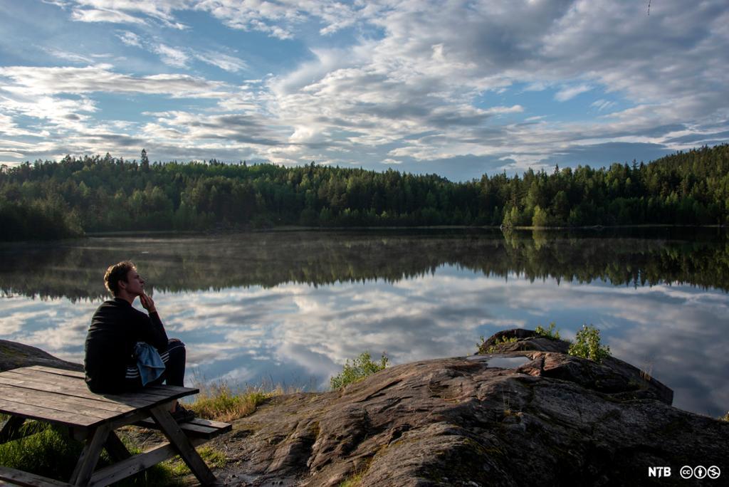 En mann sitter på et rastebord ute i naturen. Han ser ut over en innsjø. Foto.