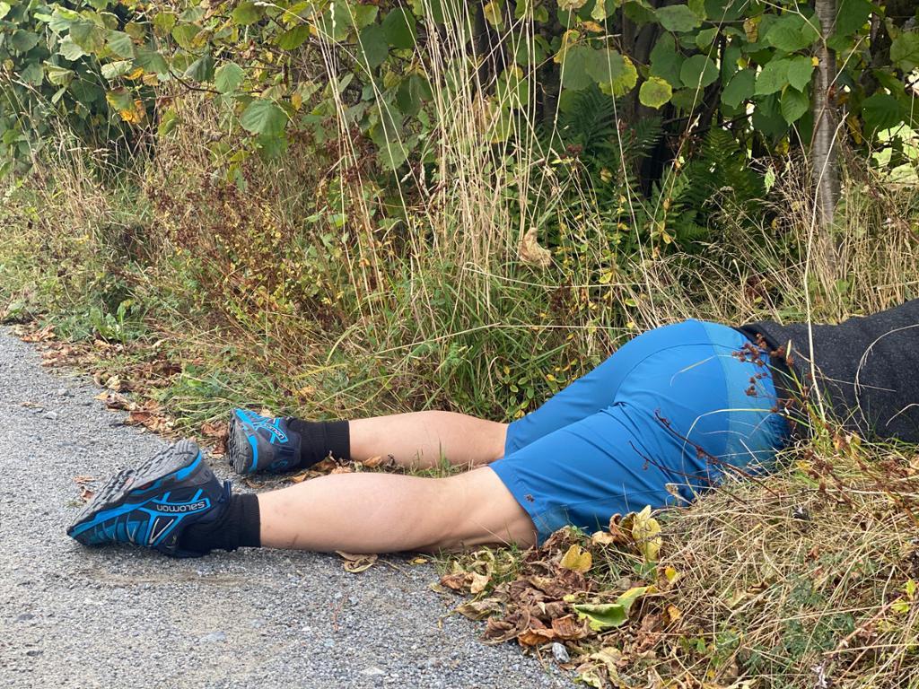 En person ligger på magen ved siden av veien med føttene i veibanen. Vi ser bare underkroppen og beina. Personen har joggesko og treningstøy. Foto.