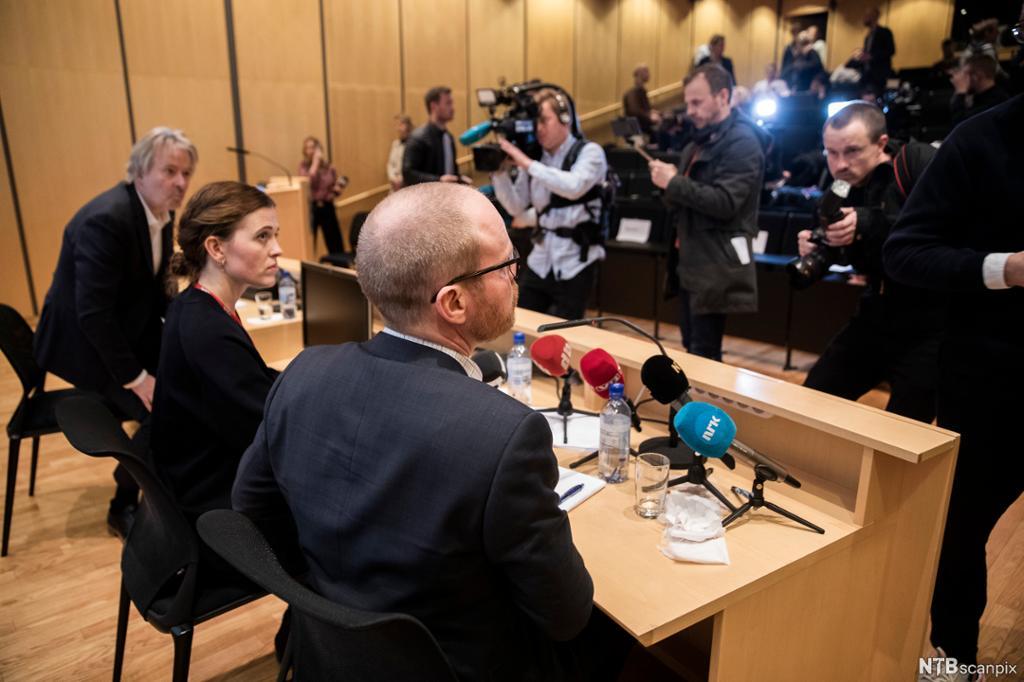 To menn og en dame ved et bord med mikrofoner foran mange journalister med kamera. Foto.