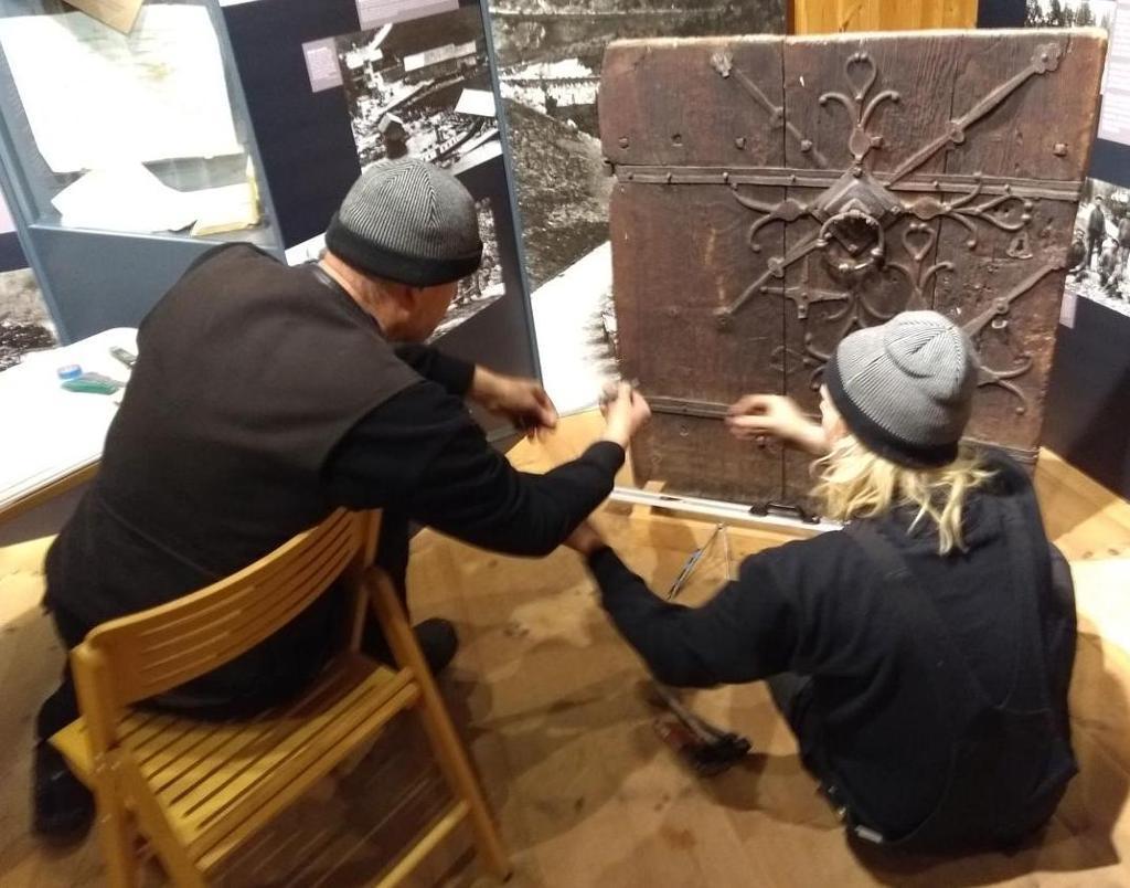 To menn samarbeider om å ta mål av et jernbeslag på ei dør. Foto.