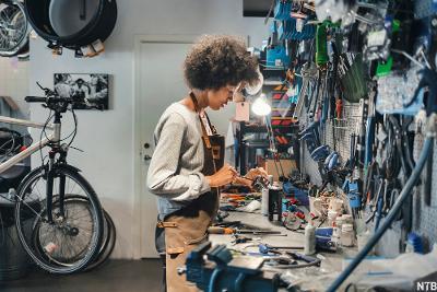 Ung kvinne smører sykkeldeler i verksted. Foto.