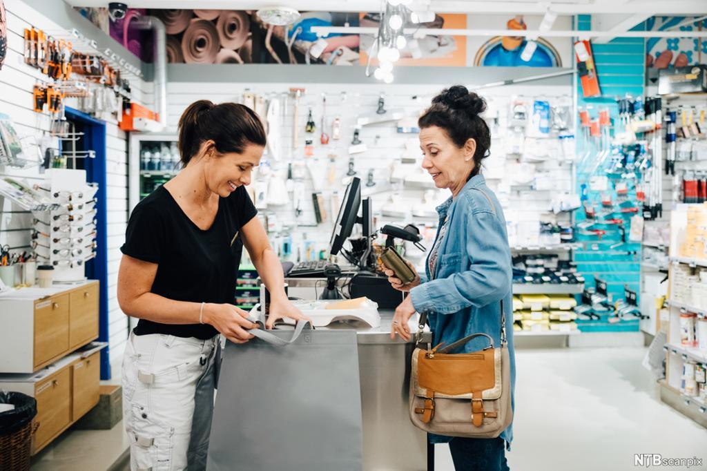 En butikkmedarbeider snakker med en kunde ved kassen. Foto.