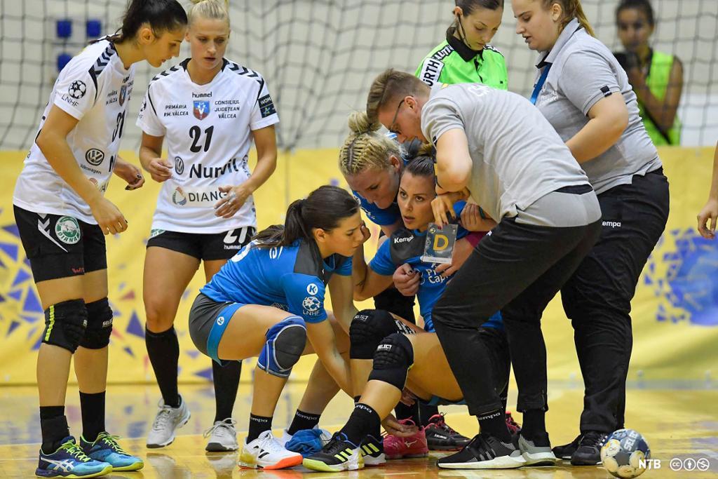 Lagvenninner og personer fra støtteapparatet hjelper håndballspilleren Nora Mørk opp fra gulvet under en håndballkamp. Foto.