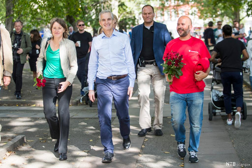 Smilende mennesker går nedover en gate. To av dem bærer buketter med røde roser. Foto.