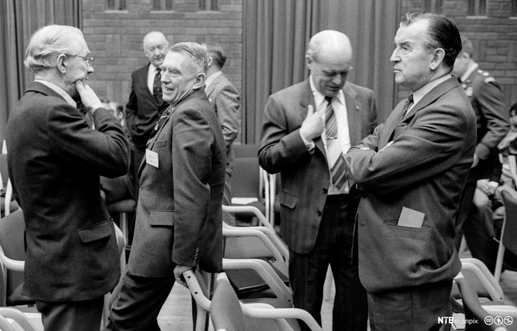 Dresskledde menn under en pause på et NATO-seminar i Oslo på 1980-tallet. Foto.