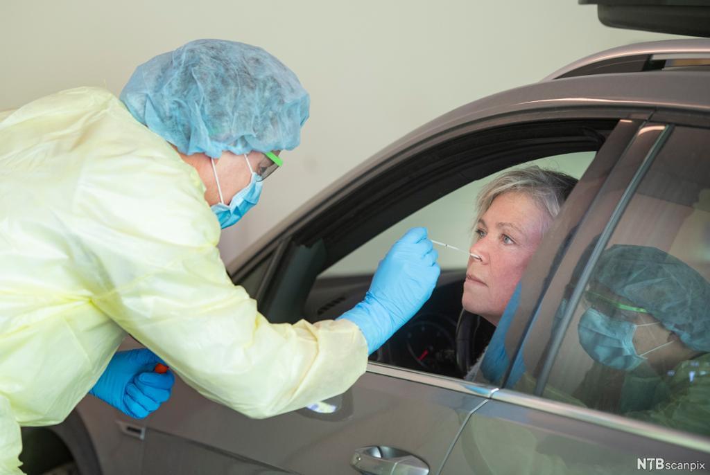 Sjukepleiar testar kvinne i bil for koronasmitte. Foto.